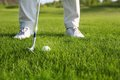 Golf club and ball in grass front of player Stock Photos