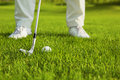 Golf club and ball in grass front of player Stock Photo
