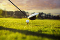 Golf club and ball in grass on tee front of driver Stock Photography