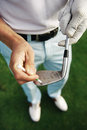 Golf club maintenace golfer removes dirt and sand from grooves of iron with a tee peg Stock Photos