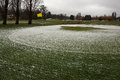 Golf course closed due to winter snow and high winds a green covered with a dusting of a yellow flag battered by wind a small Stock Photo