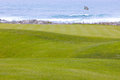 Golf course greens leading to hole by the ocean beautiful manicured on a softly rolling hilly topography putting surface is Stock Photo
