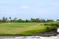 Golf course in luxury resort green field and blue sky on the background of the sea beautiful palm tree over with white clouds Stock Images
