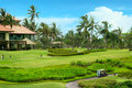 Golf course in luxury resort green field and blue sky on the background of the sea beautiful palm tree over with white clouds Stock Photo