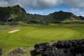 Golf course under mountains mountain in town heimaey westman islands iceland Royalty Free Stock Photography
