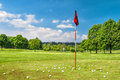 Golf field and cloudy blue sky. Spring landscape with grass and Royalty Free Stock Photo