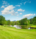 Golf field. Landscape with green grass and beautiful blue sky Royalty Free Stock Photo