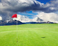Golf field with red flag in the hole Stock Image