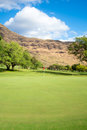 Golf green with red flag an empty course at the base of dry mountains and tropical skies Stock Images