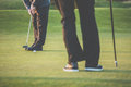 Golf green sceen golfer putting near the hole short putt colort toned image with reduced contrast and some added noise Royalty Free Stock Photo