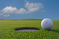 Golf hole and ball a near a a blue sky Stock Photos