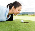 Golf player blowing ball female the into a hole Royalty Free Stock Photos