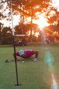 Golf player blowing ball in hole with sunset in background Royalty Free Stock Photo