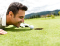 Golf player cheating by blowing the ball into a hole Royalty Free Stock Image