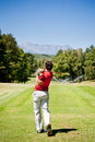 Golf player performs a tee shot using driver club one young caucasian male golfer red shirt and white pants clear summer day Stock Photography