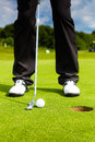 Golf player putting ball in hole into only feet and iron to be seen Royalty Free Stock Photos