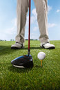 Golf player teeing up to hit ball a shot of Stock Photo