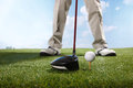 Golf player teeing up to hit ball a shot of Stock Photography