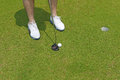 Golf player with white shoes holding a club with golf ball near Royalty Free Stock Photo