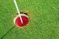 Golf practice putting green hole and marked with a red sign Royalty Free Stock Photo