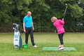 Golf pro assessing a lady golfers backswing golfer being taught to play by on practise driving range Stock Photos
