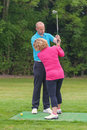 Golf pro correcting a lady golfers grip golfer being taught to play by on practise driving range Royalty Free Stock Photography
