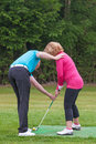 Golf pro teaching a lady golfer being taught to play by on practise driving range Stock Photo
