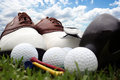 Golf shoes and equipment sitting on grass with a bright blue sky in the background Royalty Free Stock Photography