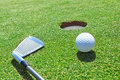 Golf stick and ball on the grass near the hole Royalty Free Stock Image