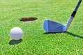 Golf stick ball near the hole against background of grass Royalty Free Stock Image