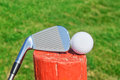 Golf stick upside down on a wooden ball pedestal the grass close up Royalty Free Stock Photography