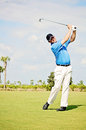 Golf swing man during on the fairway at a tropical resort Stock Photography