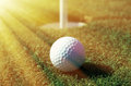 Golfball in front of the hole Royalty Free Stock Photo