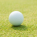 Golfball on grass infront of the green Royalty Free Stock Photography