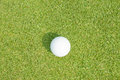 Golfball on grass infront of the green Royalty Free Stock Images