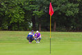 Golfer and caddy reading the line of putt a professional his looking at Stock Image