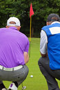 Golfer and caddy rear view. Royalty Free Stock Photo