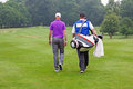 Golfer and caddy walking up a fairway towards ball on par Stock Photos