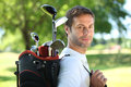 Golfer carrying clubs Stock Photography