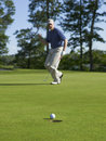Golfer celebrates sinking putt on green Stock Photography
