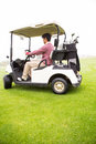 Golfer driving in his golf buggy Royalty Free Stock Photo