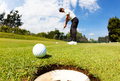 Golfer drove the ball into the hole on putting green; summer sun Royalty Free Stock Photo