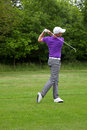 Golfer follow through male in the position after a mid iron fairway shot Stock Photos