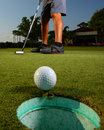 Golfer golfing and close up of golf ball on a course about to get the in the hole Stock Photo