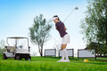 Golfer hitting golf ball attractive woman bag Royalty Free Stock Photography