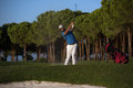 Golfer hitting a sand bunker shot on sunset Royalty Free Stock Photo