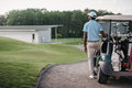 Golfer looking away while standing near golf cart Royalty Free Stock Photo