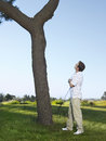 Golfer looking at ball on tree side view of young male Stock Photography