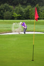 Golfer playing out of a bunker shot greenside Stock Images