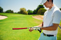 Golfer removing glove portrait of golf while holding putter on green Royalty Free Stock Photos